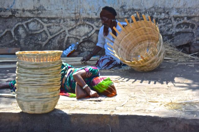 A street basket maker takes a nap